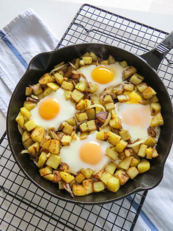 Freshly made skillet hash and eggs cooling on a wire rack.