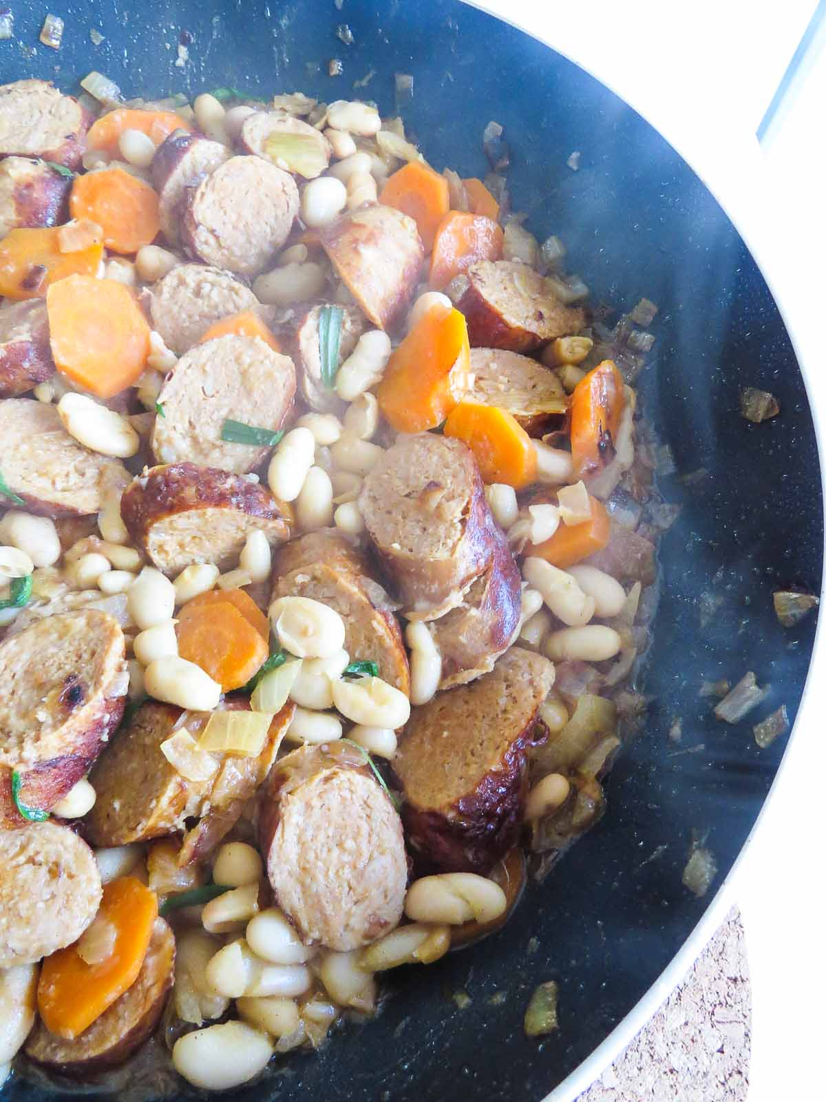 Sausage and Cannellini Beans in White Wine - Tied together with sautéed onions and carrots, this Sausage and Cannellini Bean in White Wine recipe has all the wonderful deliciousness cooking in one pan!