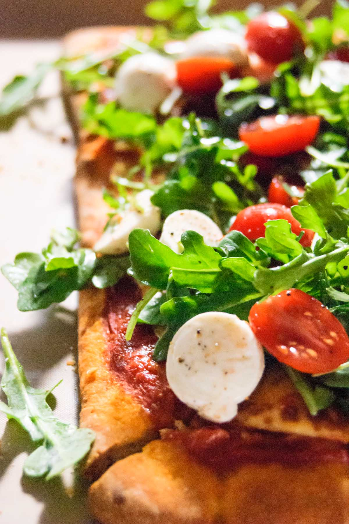 This Caprese Arugula Flatbread Pizza recipe is a date night in and a weeknight dinner miracle worker! It's Netflix binge-worthy, romantic, quick to make, great with a glass of wine, and has a good dose of greens!!! - thebeaderchef.com #pizza | #datenighin | #quick | #easy | #weeknightmeal | #flatbread | #flatbreadpizza | #boccocnini | #caprese | #capresesalad