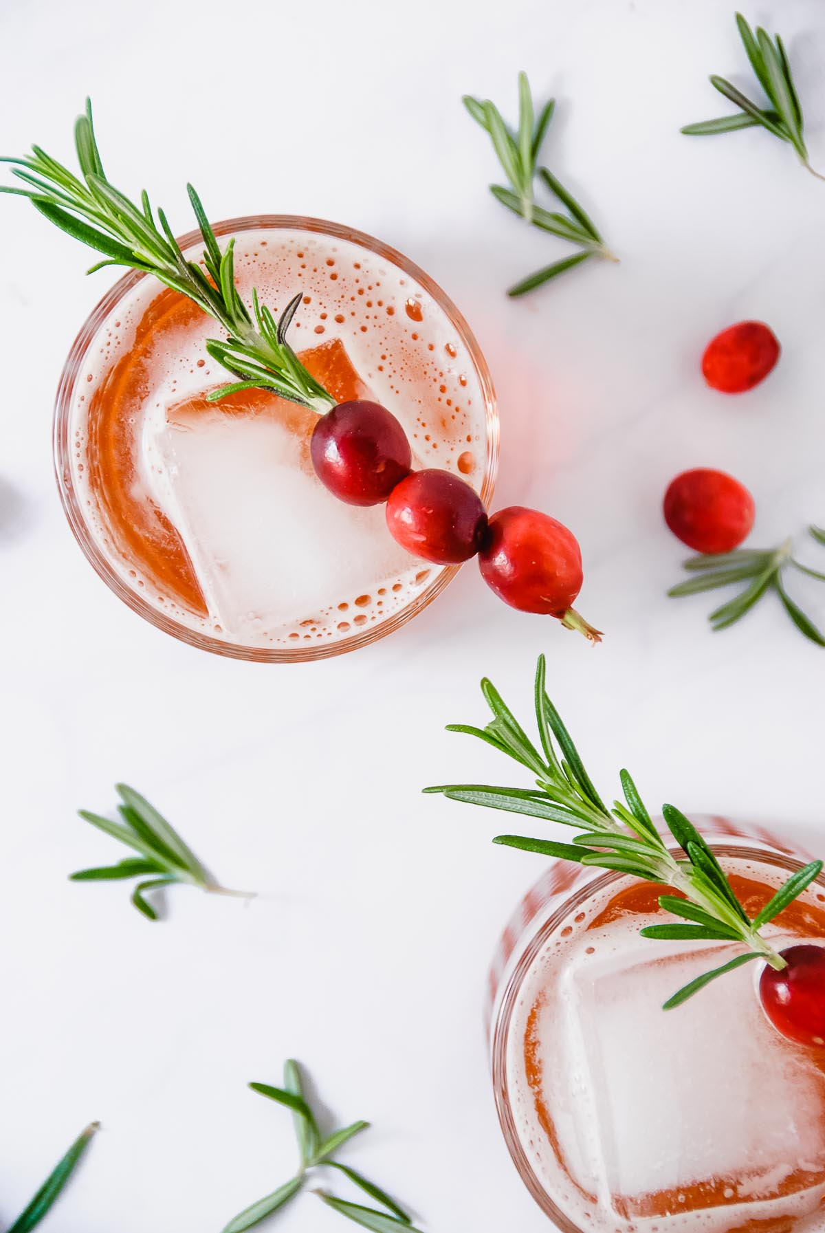 Santa's Secret Cocktail is all of the classic holiday flavours combined into one drink! Rosemary infused simple syrup, orange liquor and cranberry juice are shaken together and topped with prosecco and a cranberry rosemary skewer to make the perfect Christmas cocktail! - thebeaderchef.com #cocktail #mocktail #santa #christmas #holiday #drinks #cranberry #rosemary #orangeliquor #prosecco