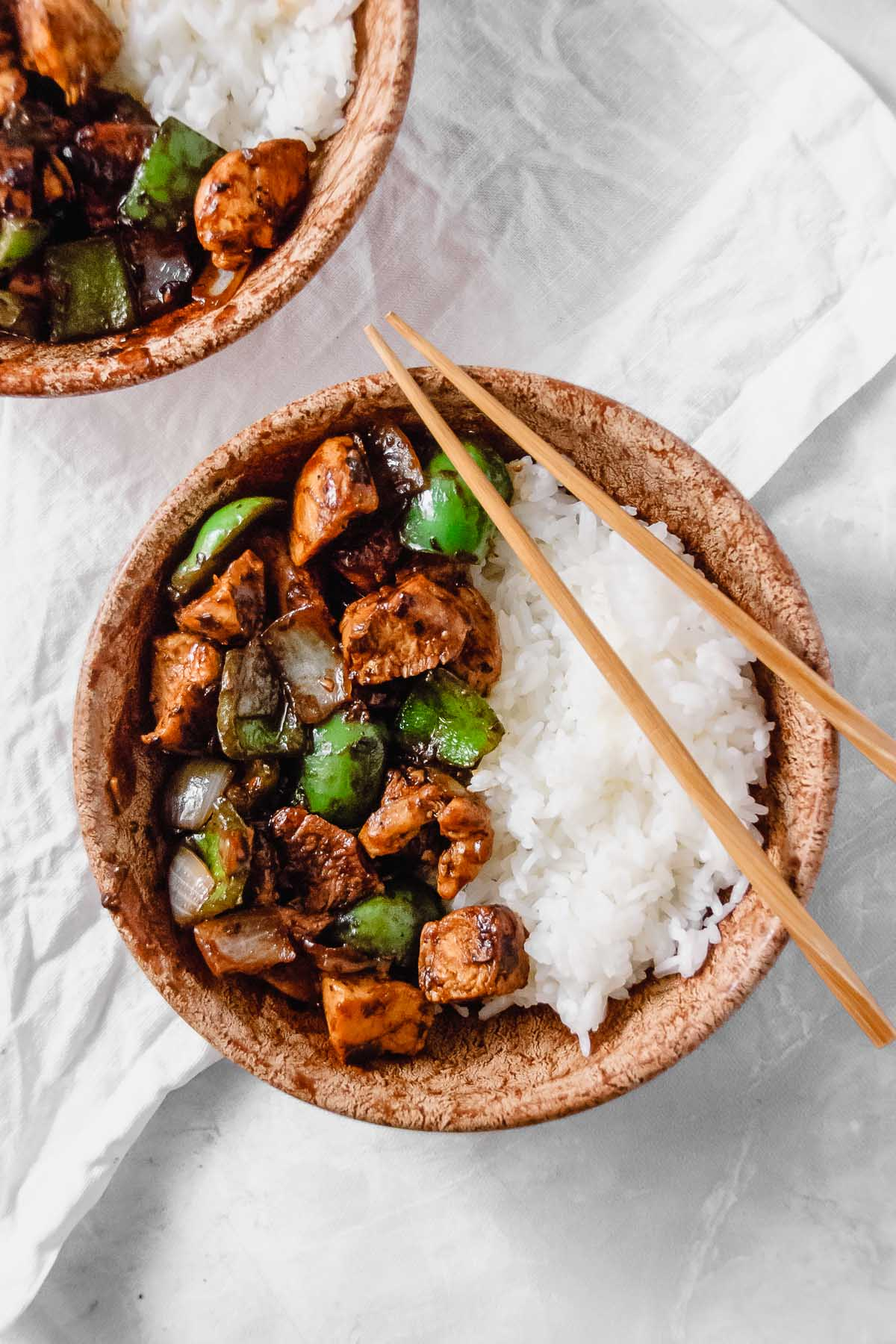 Wood bowls containing black bean chicken stir fry and rice with chopsticks and a white napkin on a grey background.