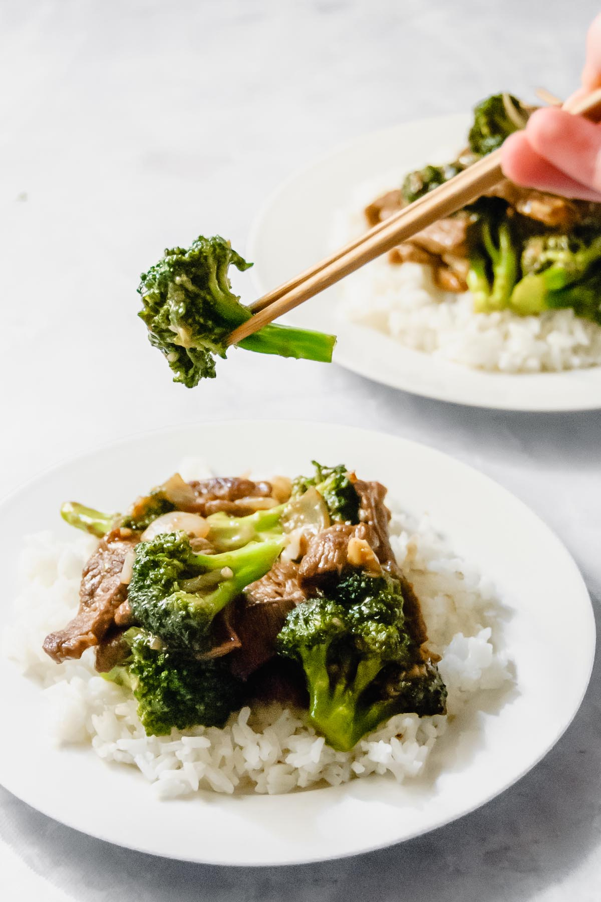 Chinese broccoli beef over rice on a white plate with chopsticks holding a piece of broccoli.