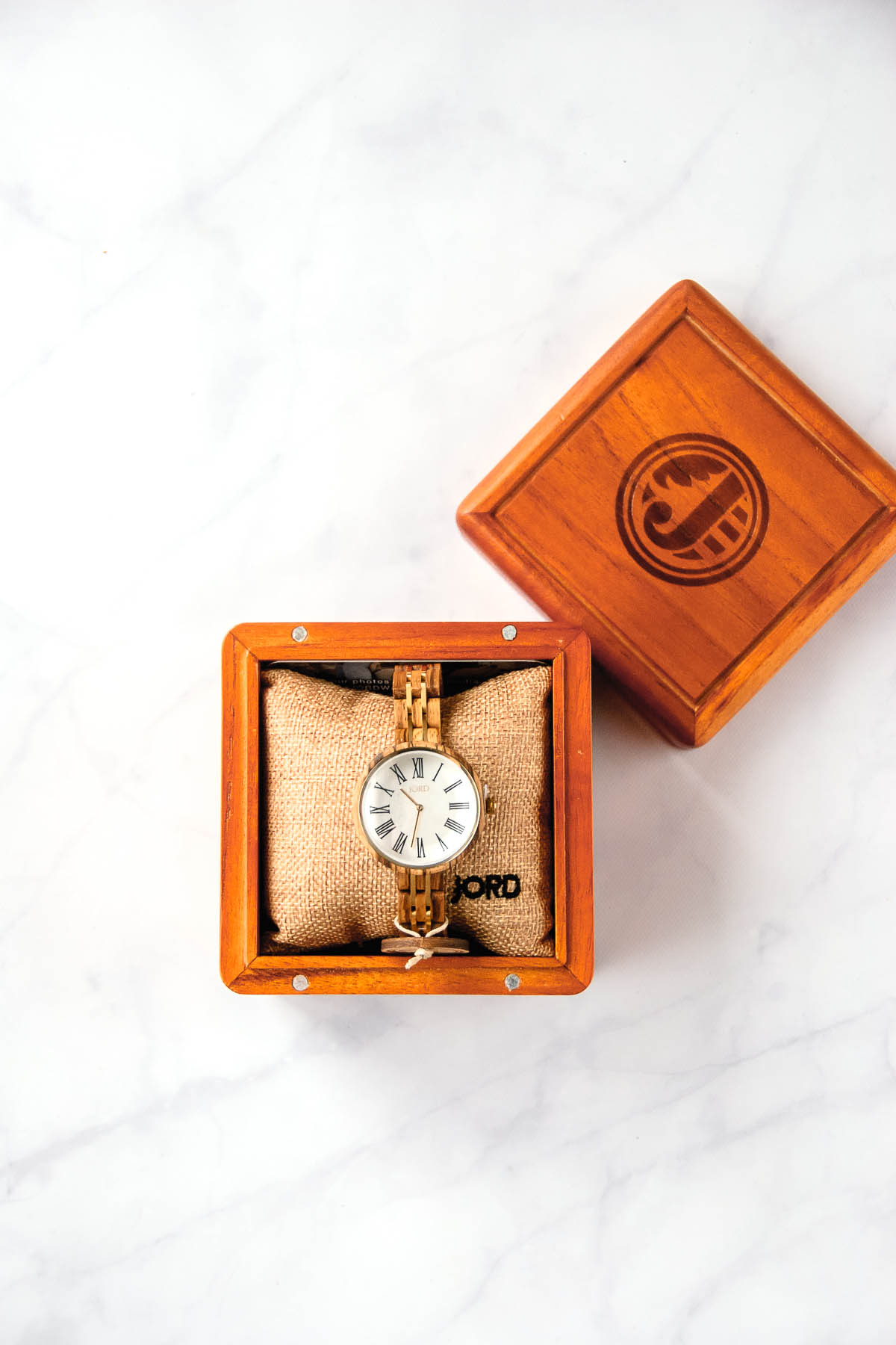The Cassia Zebra and Ivory watch made by JORD wood watch in its wood box on a marble countertop.