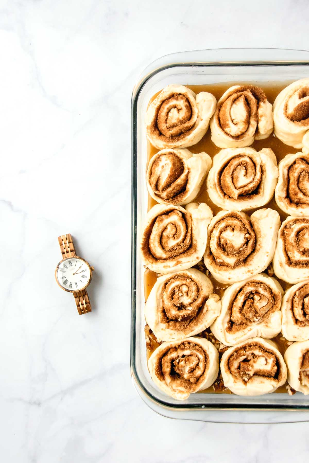 Cinnamon rolls in abaking dish before proofing beside a JORD wood watch.