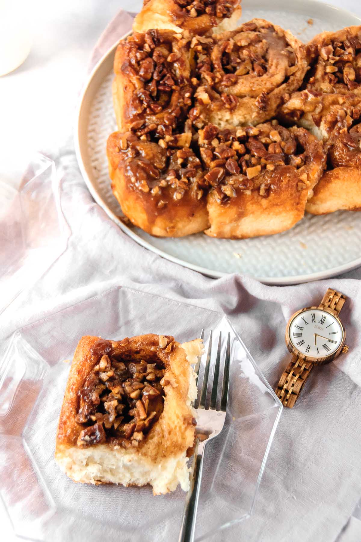 Table setting with cinnamon rolls on a platter and one cinnamon roll on a glass plate with a JORD wood watch beside it.