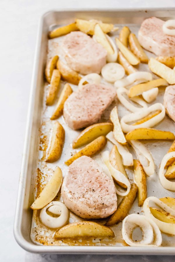 Sheet Pan Pork Chops & Potatoes: Sheet pan with pork chops, fingerling potatoes and onions tossed in oil, salt and pepper.