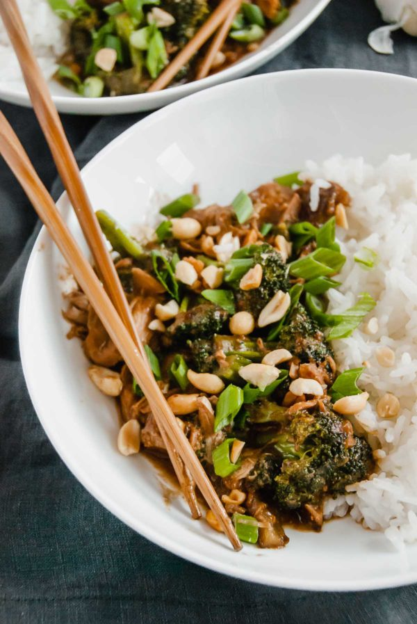 Two plates of slow cooker thai peanut chicken served with rice and topped with peanuts and sliced green onions.