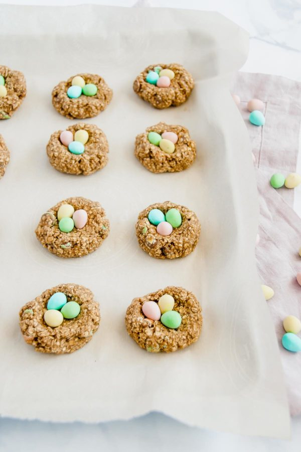 Small batch mini egg oatmeal cookie dough rolled into balls on a parchment paper lined cookie sheet with mini eggs on top.