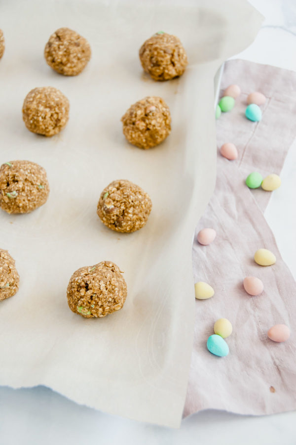 Small batch mini egg oatmeal cookie dough rolled into balls on a parchment paper lined cookie sheet.