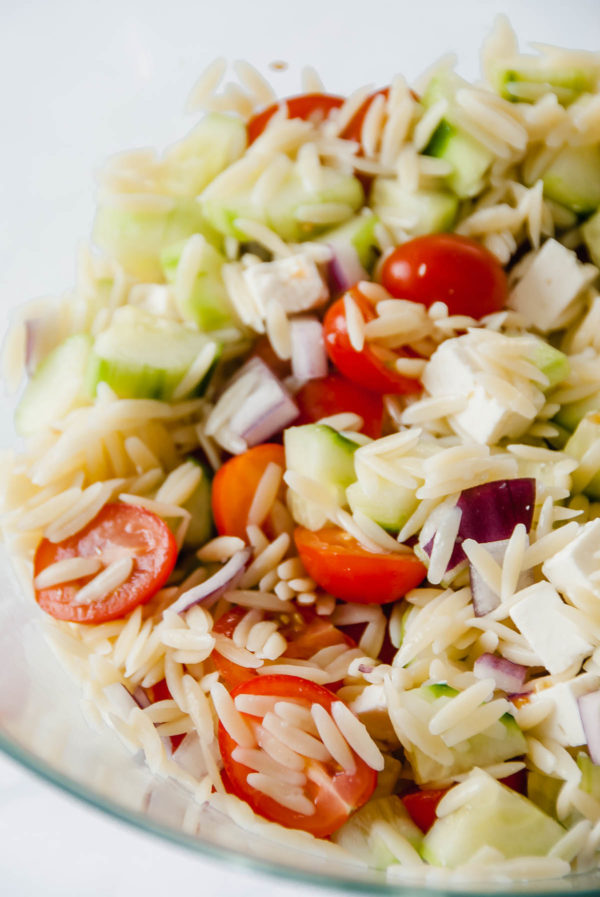 Close up of a large salad bowl containing cherry tomatoes, cucumbers, orzo, red onion and feta to make Mediterranean Orzo Salad.