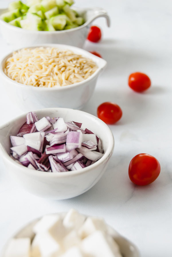 Prep bowls filled with cucumbers, orzo, red onion and feta to make Mediterranean Orzo Salad.