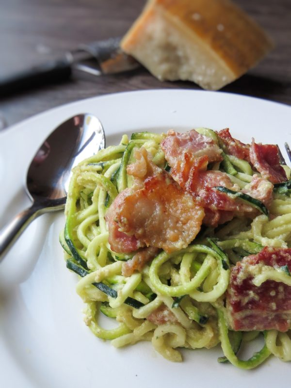 A plate with classic carbonara with zucchini noodles on a wood table with parmesan cheese.