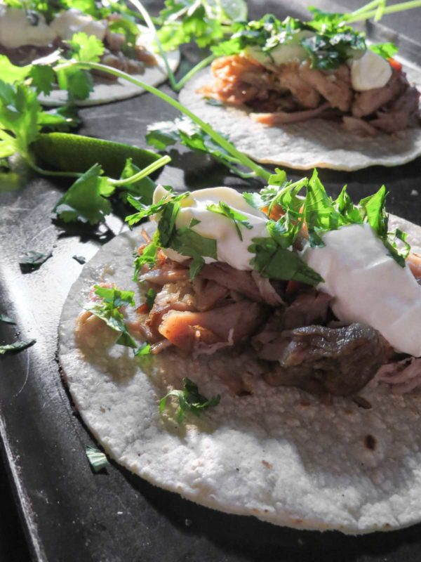 Papa's sous vide carnitas dressed up on a platter with sour cream and cilantro.