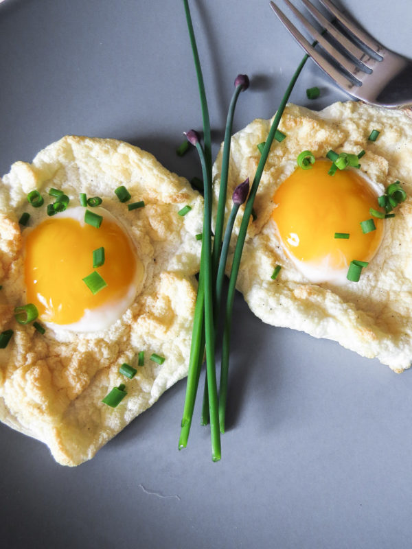 Two cloud eggs on a grey-blue plate with chives on top.