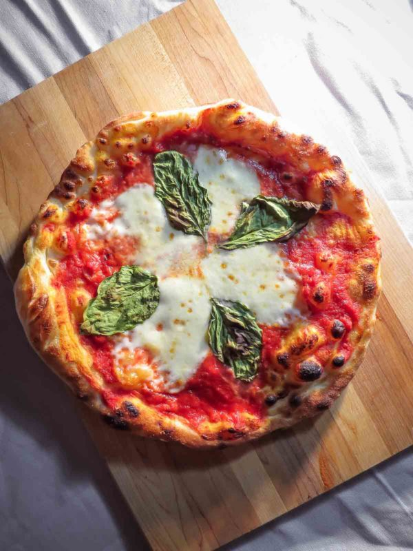 Skillet napolitana pizza fresh out of the oven on a wood cutting board.