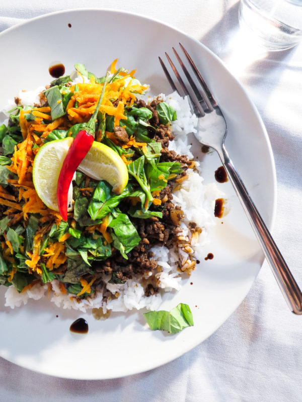 Plate of Thai red chili basil beef served on rice with lime wedges.