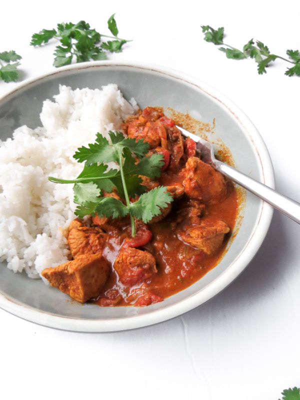 A dish with awesome chicken tikka masala served along side basmati rice.