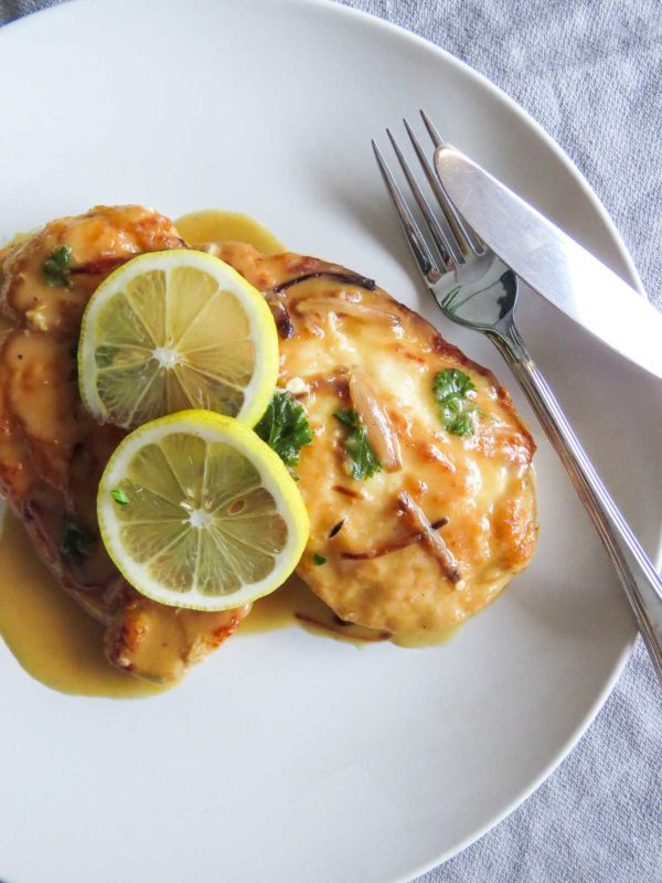 Chicken piccata on a plate with a fork and knife leaning against the plate.