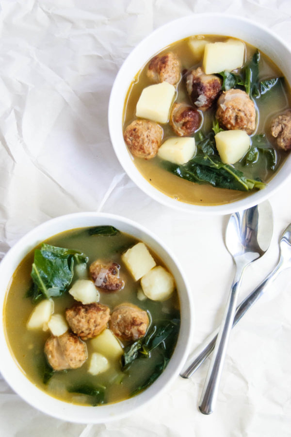 Two bowls of caldo verde soup beside two spoons.