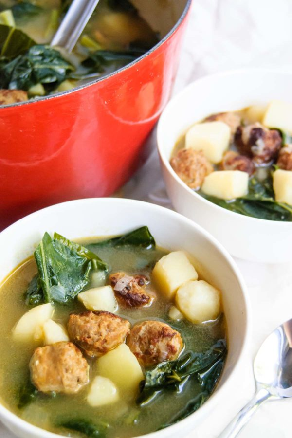Two bowls of caldo verde soup next to a red dutch oven used to cook the soup.