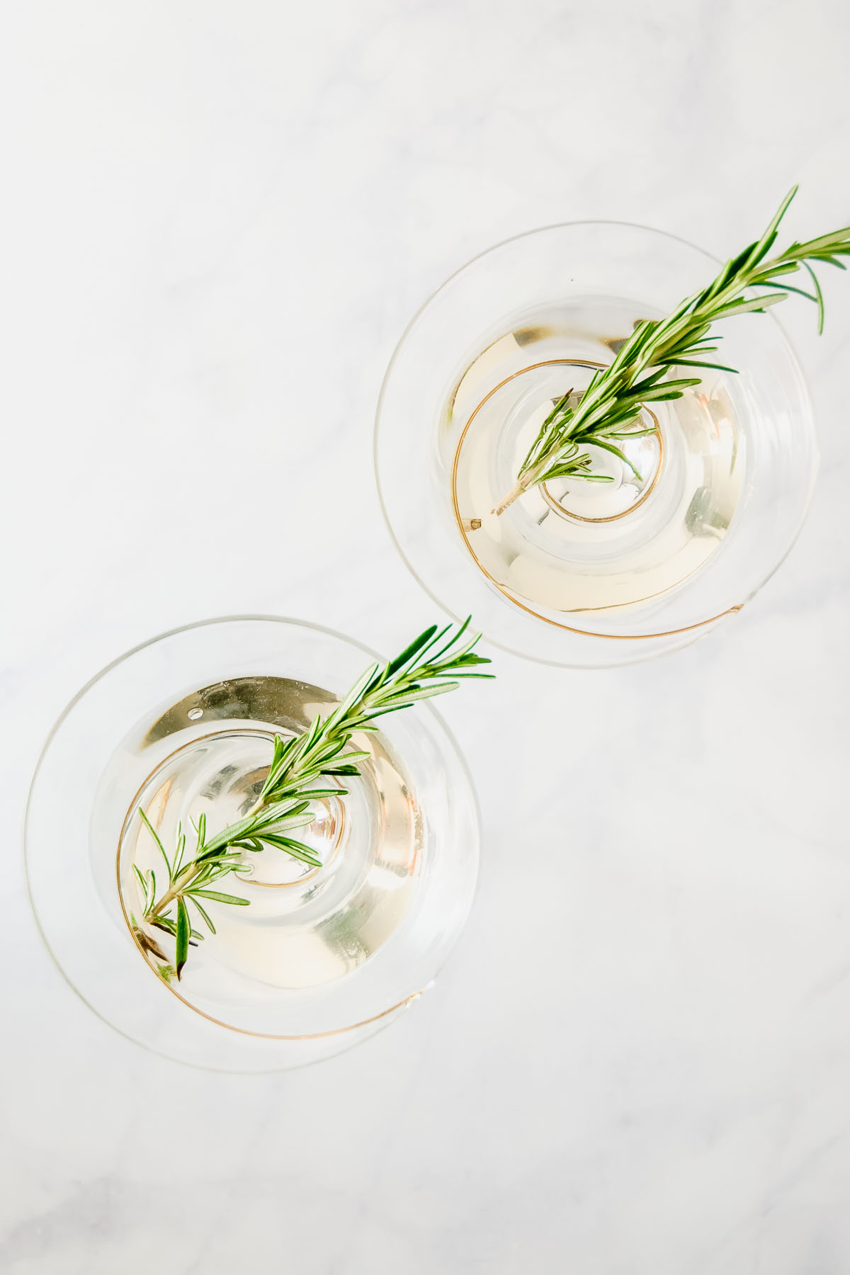 Simple and elegant, an O'Christmas Tree Martini will become your go-to holiday gin martini. PS. it's flavored with rosemary! - thebeaderchef.com #gin #martini #christmas #holiday #cocktail #mocktail #rosemary