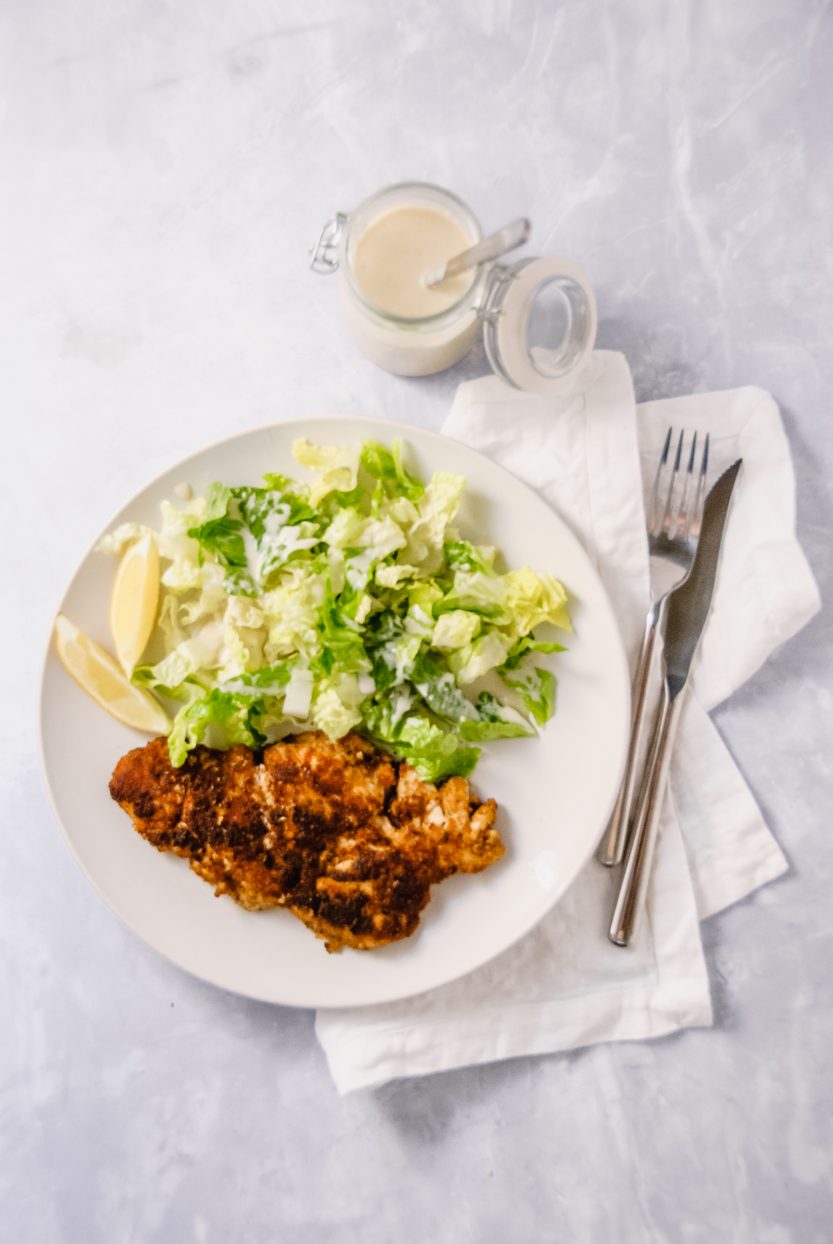 White plate with a caesar salad: romaine lettuce and light caesar salad dressing, lemon slices and chicken cutlets: breaded chicken fried in garlic infused oil.