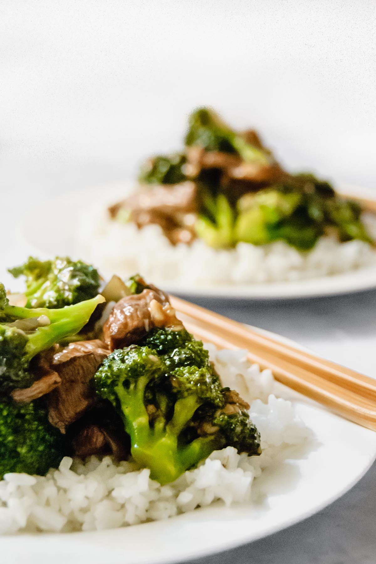 Chinese broccoli beef over rice on a white plate with chopsticks.