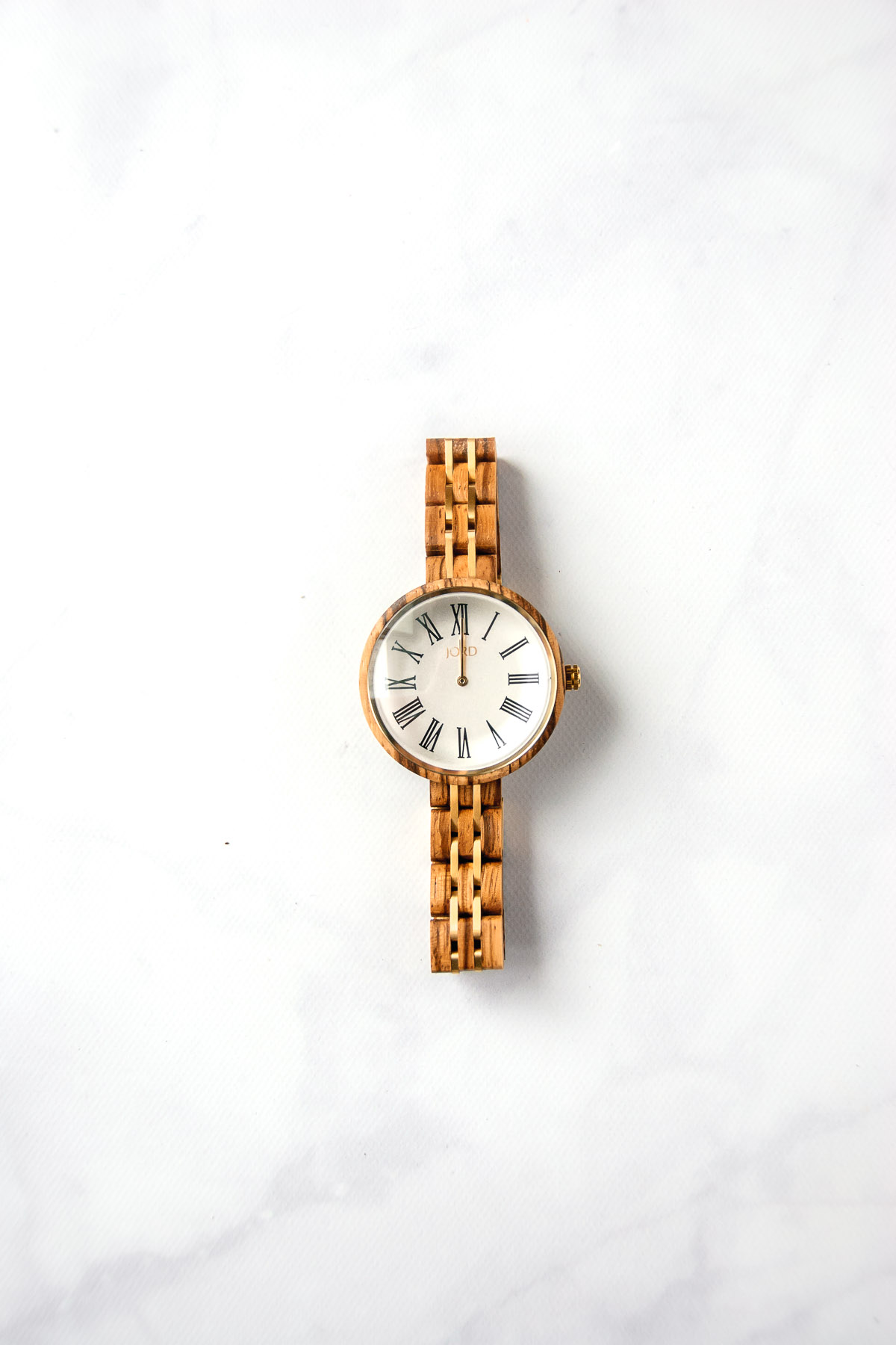 Close up of the Cassia Zebra & Ivory wood watch by JORD on a marble countertop.