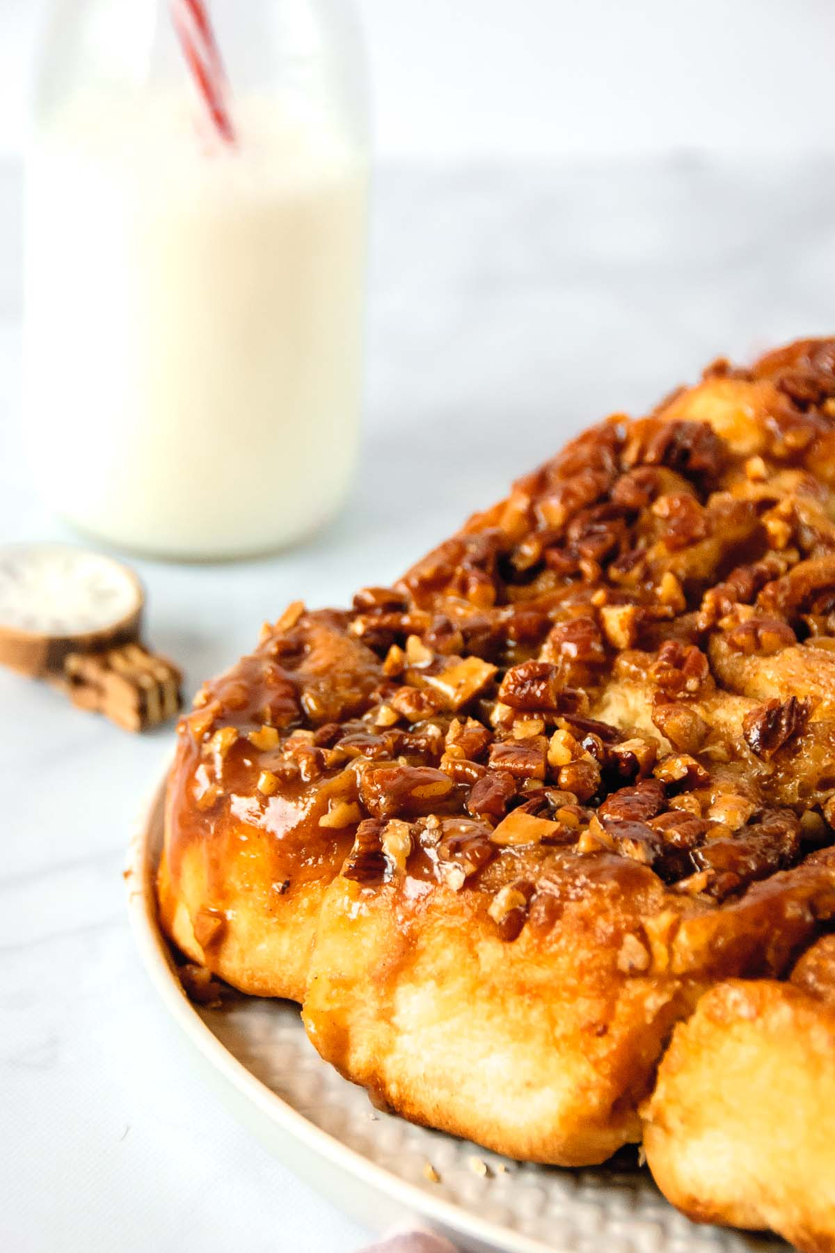 Close up of cinnamon rolls with a jug of milk and a JORD wood watch in the background.