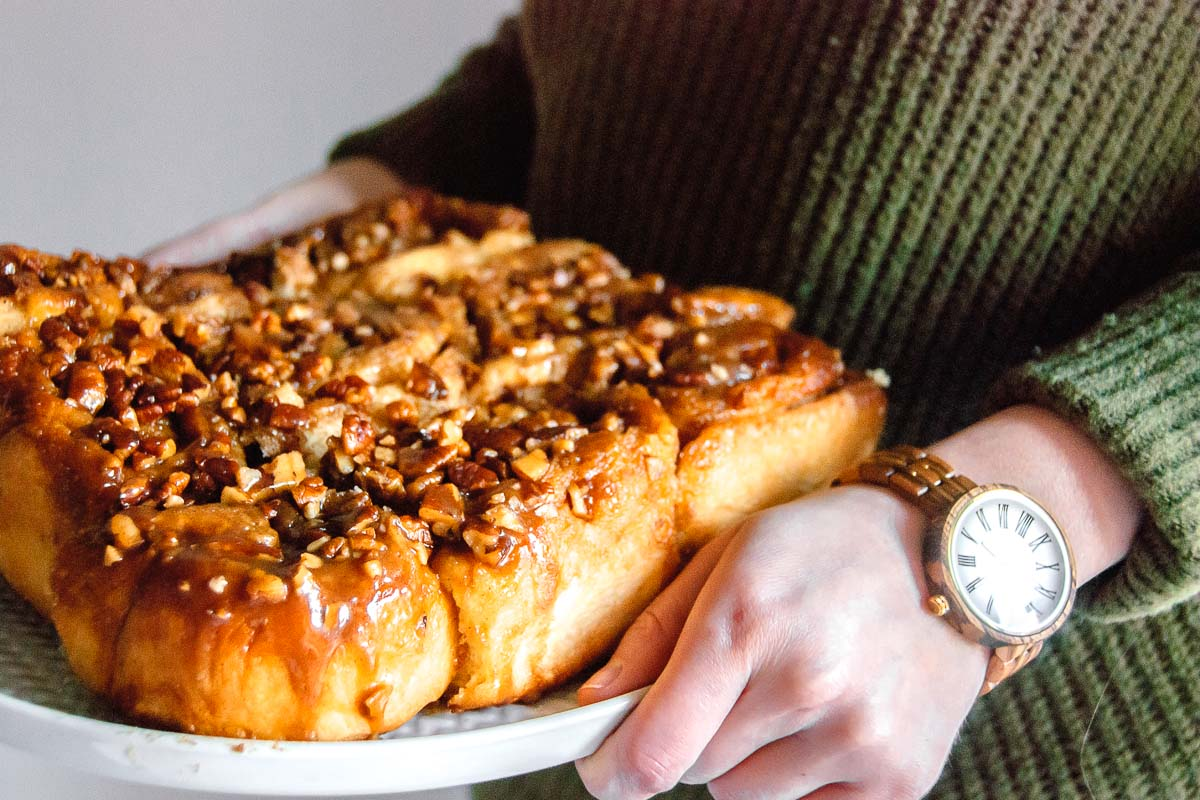 Woman wearing a JORD wood watch while holding a platter of cinnamon rolls.