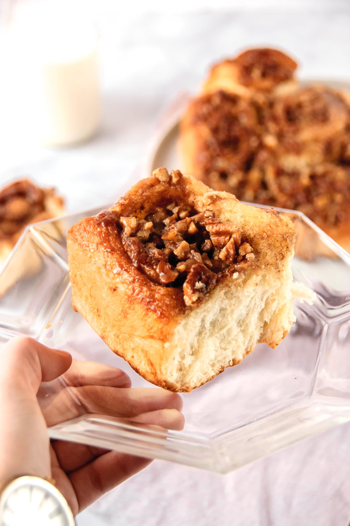 Cinnamon roll on clear glass plate being held by a hand wearing a wood watch and a platter of cinnamon rolls in the background.