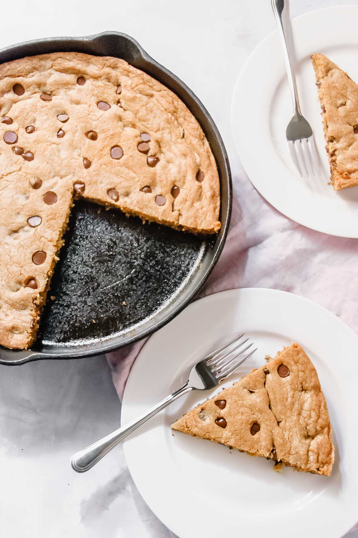 Giant chocolate chip skillet cookie served on two white plates.