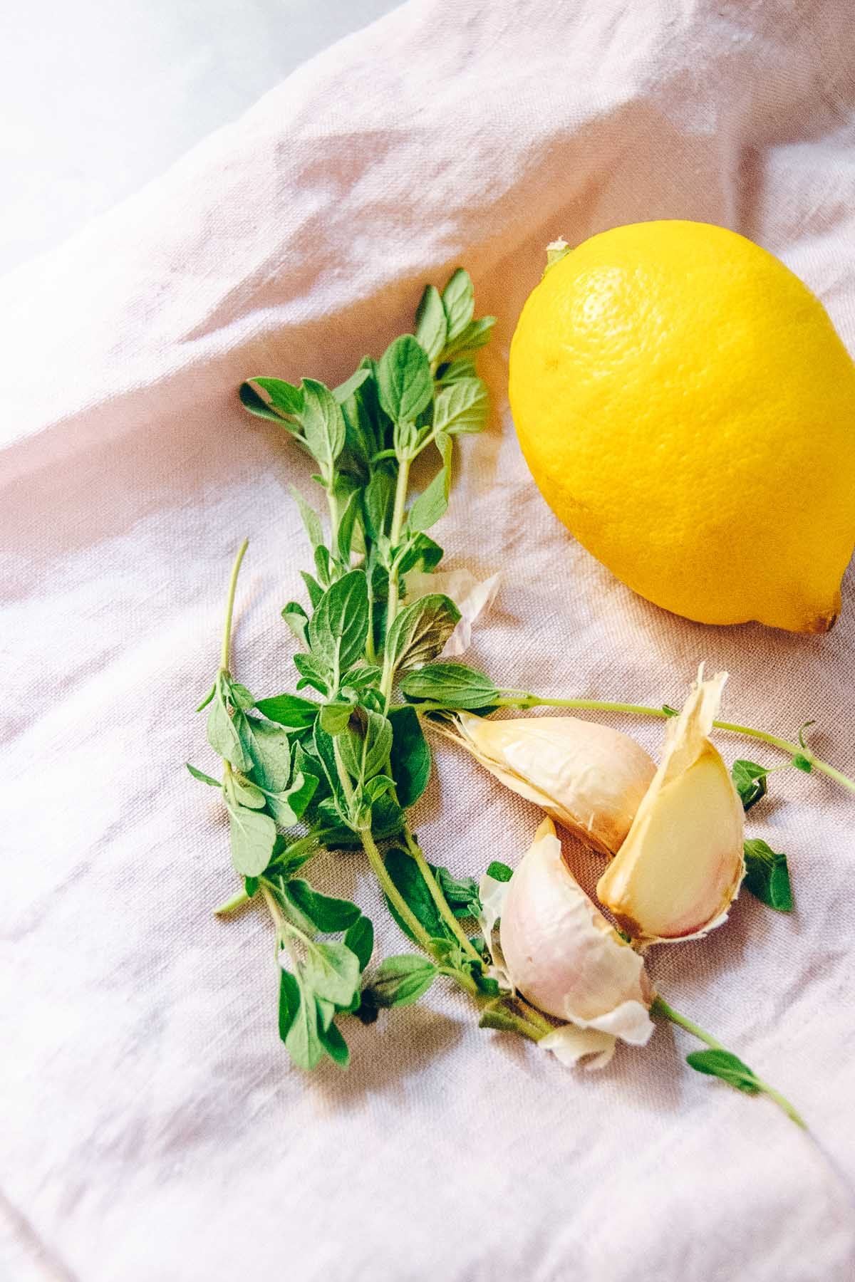 A lemon, fresh oregano and three cloves of garlic on a pink napkin.
