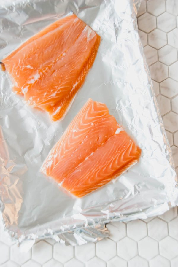 Two fillets of salmon on a tin foil lined quarter baking sheet ready to be dressed in the sauce for baked asian salmon for two.
