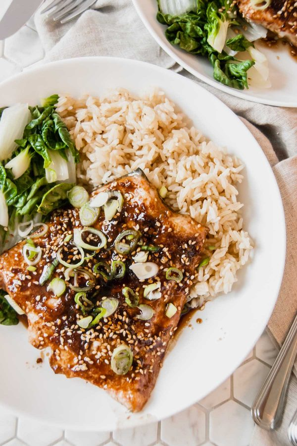 Plate of baked asian salmon for two served on a white plate with steamed bok choy and brown rice.