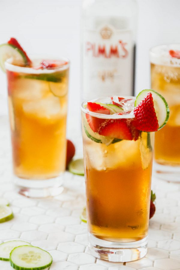 A Pimm's cup in the foreground and other Pimm's cup in the background with a bottle of Pimm's no. 1.