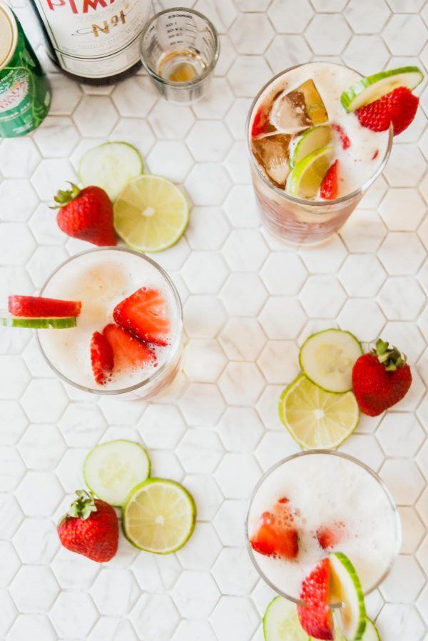 Overhead view of three glasses of Pimm's cup with a bottle of Pimm's no. 1 and ginger ale in the top lefthand corner.