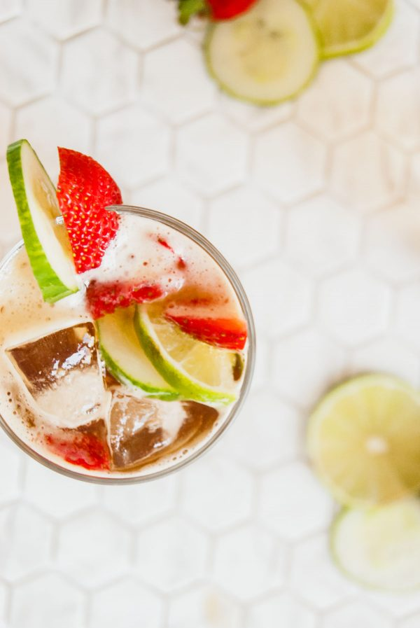 Overhead view of a Pimm's cup glass garnished with a cucumber slice and a strawberry.