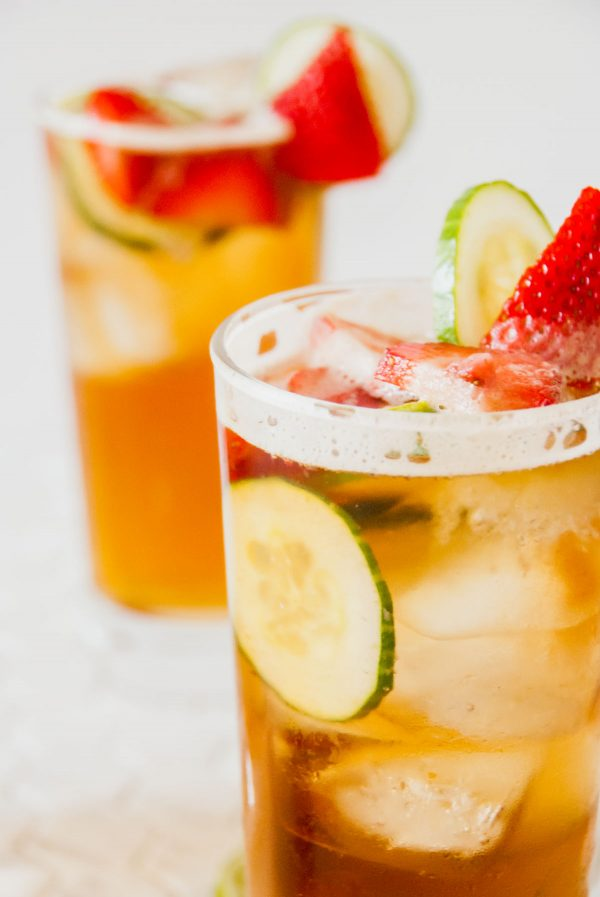 Close up of a Pimm's cup garnished with a cucumber and a strawberry and with another cup in the background.