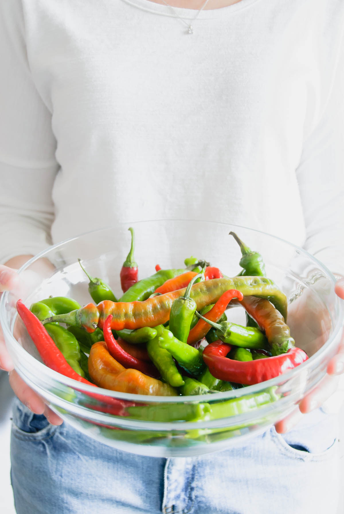 A woman holding a bowl of peppers ready to be cooked for 5-minute charred peppers.