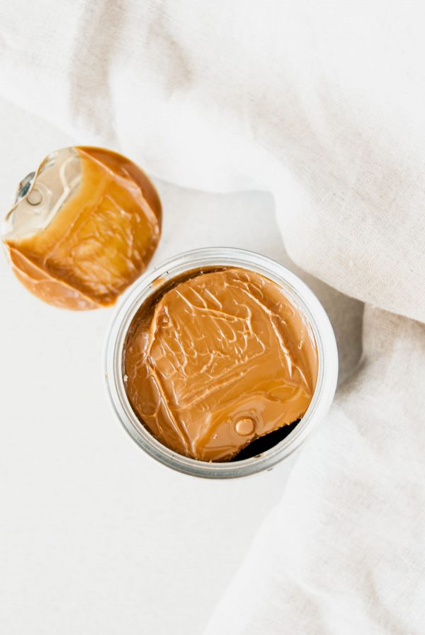 A view of an opened can of slow cooker dulce de leche with the cover beside it.