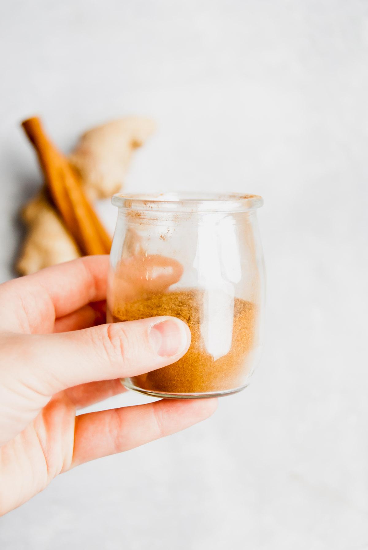 A hand holding up a jar of fall spice blend (aka pumpkin spice).