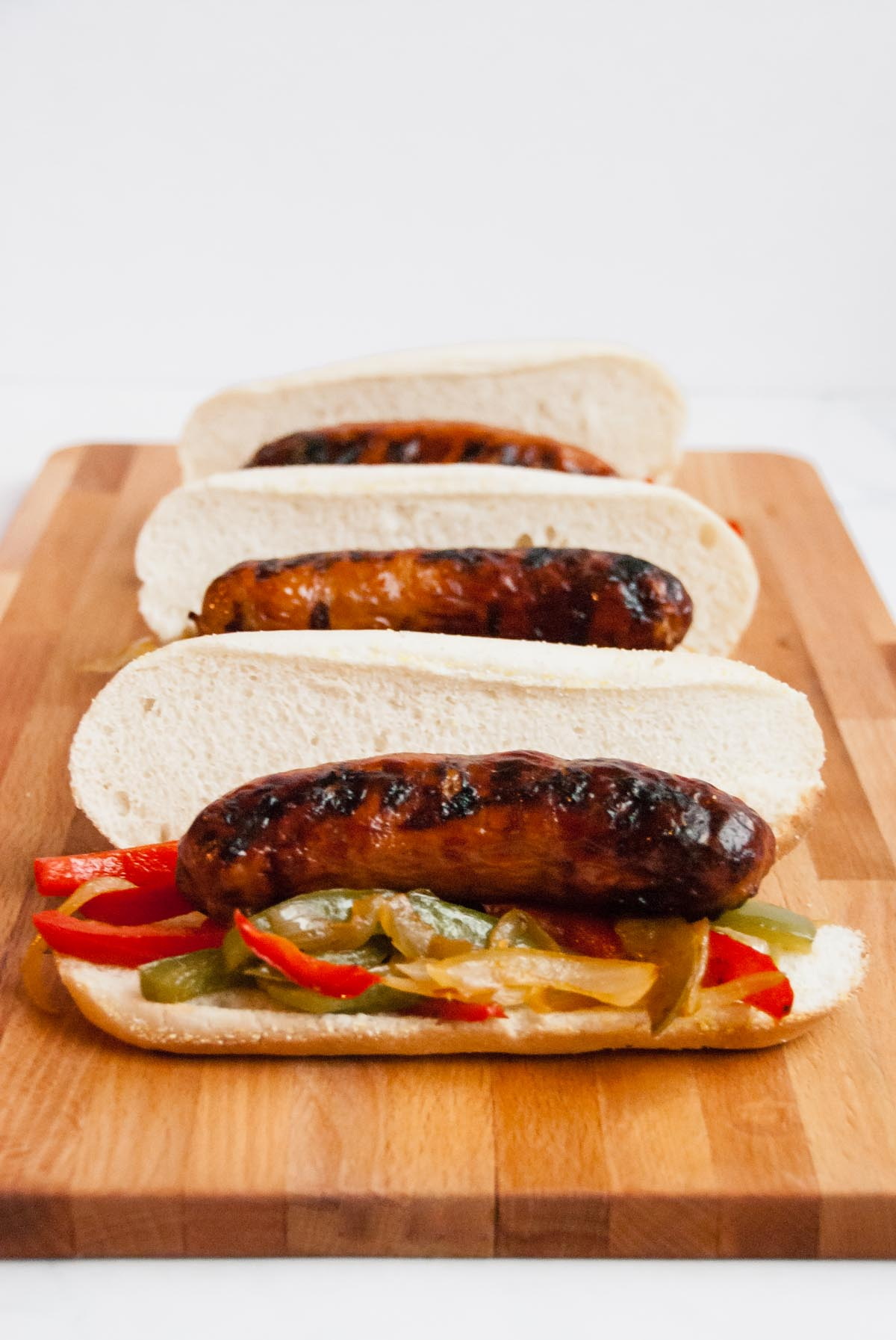 Three Italian sausage subs on a wood cutting board ready to be served.