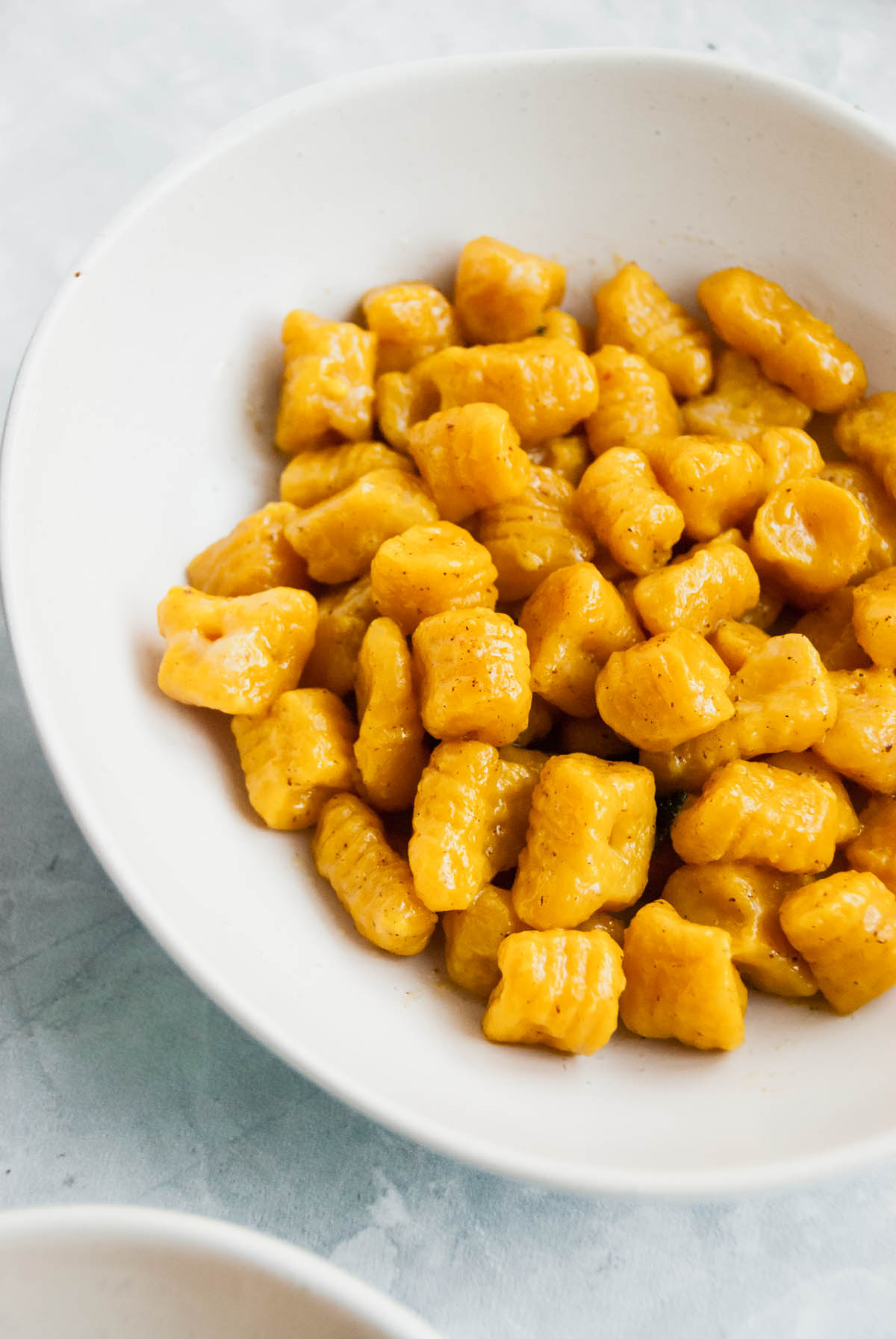 Close up of squash gnocchi in a pasta bowl.