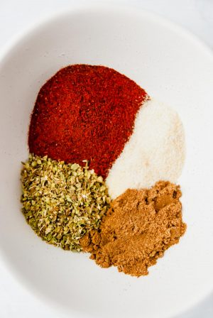 Bowl containing chili powder, oregano, garlic salt and cumin ready to be mixed for tex mex spice mix.