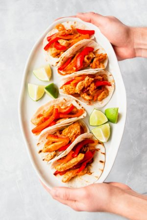 Two hands holding a plater of chicken fajitas.