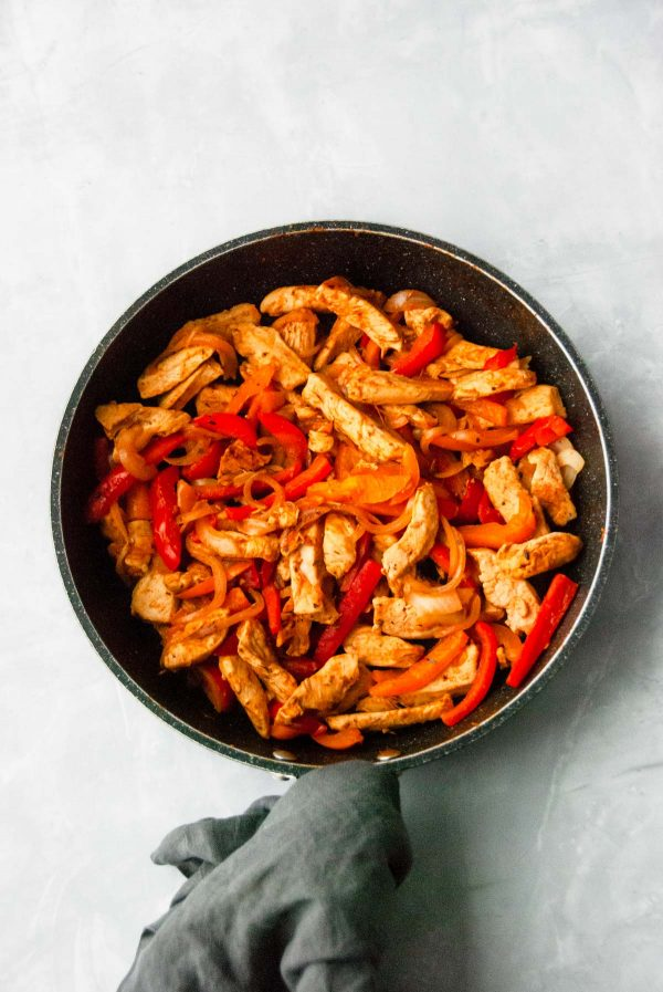 Cooked mixture of chicken, bell peppers and onions for chicken fajitas.