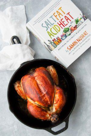 Buttermilk marinated roast chicken in a cast iron pan next to the book Salt, Fat, Acid Heat.