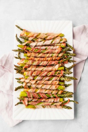 A platter of bacon-wrapped asparagus placed on a napkin ready to be served.