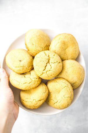 Hand holding up a dish full of soft and chewy snickerdoodles.